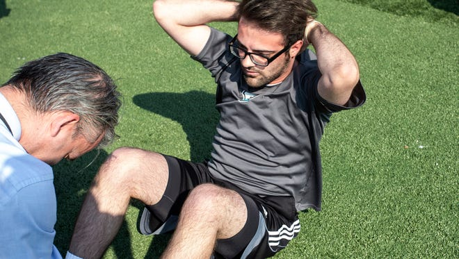 Courier Journal writer Gabe Hauari cranked out sit-ups during an FBI physical fitness qualification test on Tuesday morning. 8/14/18