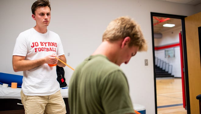 Jo Byrns athletic trainer Alex West helps a player complete rehab for an injury at Jo Byrns High School Monday, Aug. 20, 2018, in Cedar Hill, Tenn.