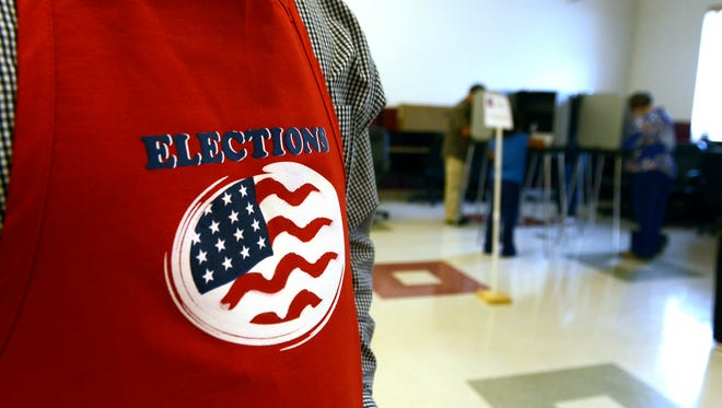 A campaign worker stands guard at a polling place near Warren Wilson College Tuesday Nov. 4, 2014.