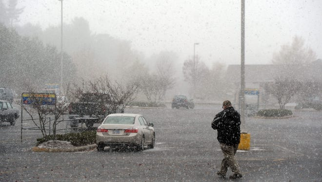 A man walks through the blowing snow towards Ingles in Weaverville Tuesday morning Nov. 18, 2104.