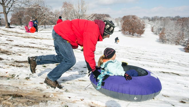 John Vella gives daughter Alice an assist on her sledding descent down Baringer Hill in Cherokee Park on Monday morning. 11/17/14