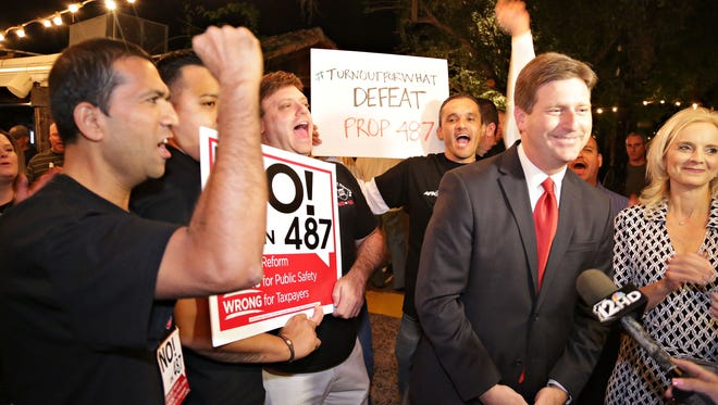 Phoenix Mayor Greg Stanton and his wife Nicole talk to the press with a group of firefighters behind them as an apparent defeat of Prop. 487 is discussed at Aunt Chilada's in Phoenix on Nov. 4, 2014.
