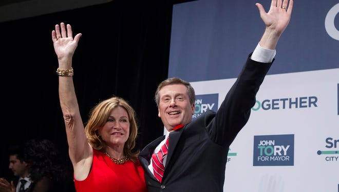 Newly elected Toronto Mayor John Tory, right, stands with his wife, Barbara Hackett, as he waves to supporters at a rally after winning the municipal election in Toronto on Monday, Oct. 27, 2014.