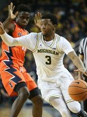 Michigan guard Zavier Simpson drives against Illinois
