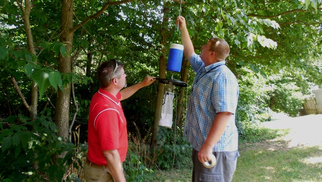 Logan Calhoun and Ben Avery, of the Ross County Health District, check mosquito traps back in 2016. Mosquitoes caught in such a trap on Allen Avenue this month have tested positive for carrying West Nile virus.