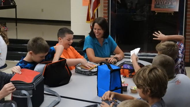 Ridgewood Middle School Principal Trista Claxon talks with fifth-graders during their lunch Tuesday, the first day of the new school year.
