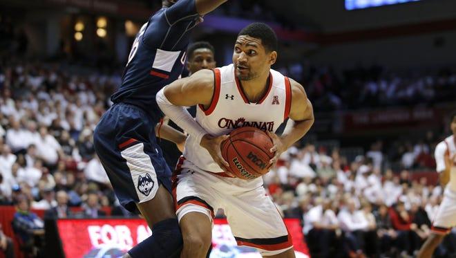 UC forward Kyle Washington (24) spins toward the basket.