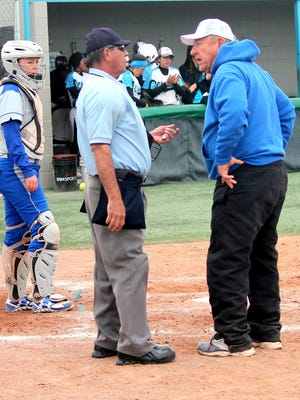 Carlsbad coach John Tigert protests a base hit call in the seventh inning on Saturday. The officials ruled that the ball went off Mackenzie Pineda's glove before entering foul territory, making it a fair ball.