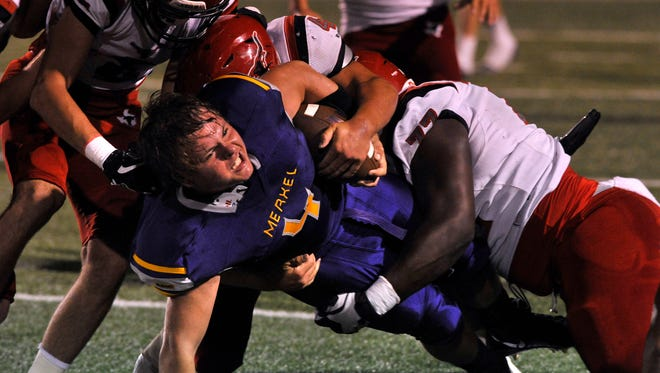 Merkel High School running back Jakob Dearing pushes for extra yardage against Eastland, despite losing his helmet earlier in the play Thursday August 31, 2017. But even Dearing's athleticism couldn't help the Badgers fend-off the Mavericks; Eastland won Thursday night's Champion's Classic Football Weekend game, 42-20.