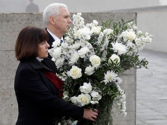 U.S. Vice President Mike Pence and his wife Karen, left, lay a wreath during a visit to the former Nazi concentration camp in Dachau near Munich, southern Germany, Sunday, Feb. 19, 2017, one day after he attended the Munich Security Conference. (AP Photo/Matthias Schrader)
