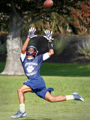 Pittsford receiver Zuril Hendricks goes all out to pull in a long throw down the sidelines during the team's practice Tuesday, Aug. 19, 2014 at Pittsford Mendon High School.