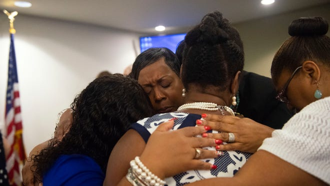 Karen Crosby, center, embraces four other black women golfers along with supporters in prayer, following the end of the second day of the human relations commission hearing on Friday regarding events at the Grandview Golf Course.