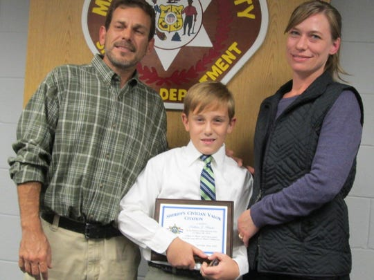 Nathan Hawke (center) with his parents Robert and Susan Hawke. Hawke was recently honored by Manitowoc County Sheriff's Office for helping to save his 6-year-old cousin's life in August.