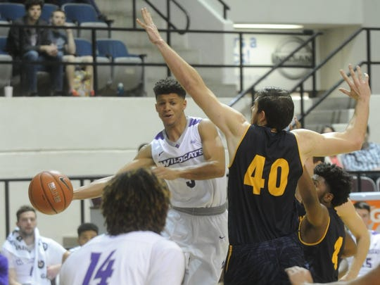 ACU's Payten Ricks, center, passes the ball under pressure from Howard Payne's Bingham Thomas (40). ACU beat the Yellow Jackets 71-55 Sunday, Nov. 27, 2016 at Moody Coliseum.