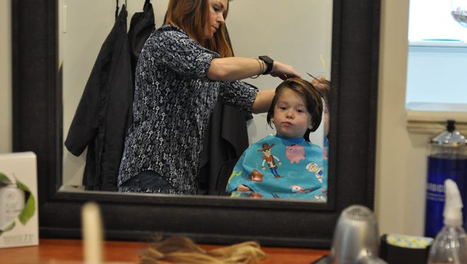 Reagan Sweat, 4, checks out his first haircut. Ponytails 12 inches long sit nearby on the table and will be donated to the nonprofit Wigs for Kids.