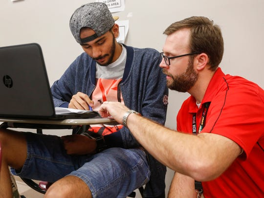 Ammar Bukhari, left, works with William Bruner, an English Language Learner Specialist, on an assignment during class at Central High School on Tuesday, Feb. 20, 2018.