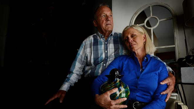 Bruce and Betty Mason hold the urn they forced their daughter to pick out while she was in active drug addiction. The parents made Katy Mason plan her own funeral a couple of years ago.