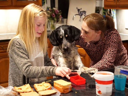 In this photo taken on Thursday, Feb. 23, 2017, 10 year-old Anna Thulin-Myge makes sandwiches with her mother Siri Oline Myge watched by their dog Birken at their home in Haugesund, Norway. Anna was born a boy but is now legally a girl. Only Malta and Norway allow children to swap gender without a doctor's agreement or intervention. She says changing in the girls' locker room and using the girls' bathroom at school makes her feel included.