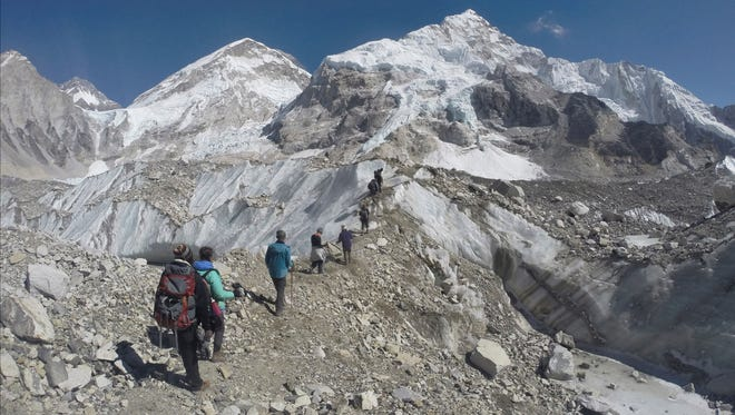 In this Feb. 22, 2016, file photo, international trekkers pass through a glacier at the Mount Everest base camp, Nepal.