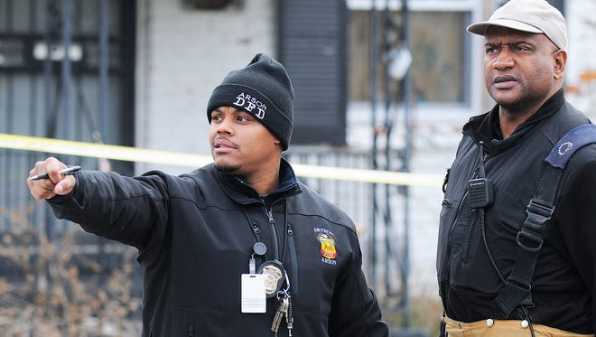 Fire Lt. James Hill-Harris, left, discusses a Detroit arson crime scene with Capt. Winston Farrow. Since joining the Arson Squad in 2011, Hill-Harris has become one of the most visible members of the Detroit Fire Department.