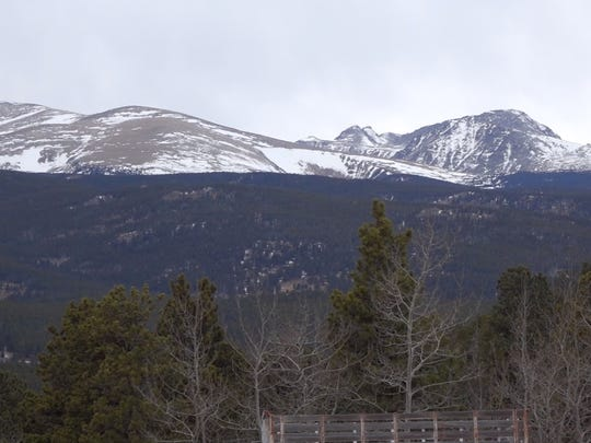 The snow-capped Indian Peaks loom over the area near