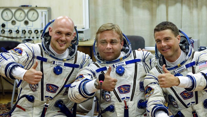 European Space Agency's astronaut Alexander Gerst, left, Russian cosmonaut Maxim Suraev, center, and NASA astronaut Reid Wiseman, crew members of the mission to the International Space Station, ISS, gesture prior the launch of Soyuz-FG rocket at the Russian leased Baikonur cosmodrome, Kazakhstan, Wednesday, May 28, 2014.