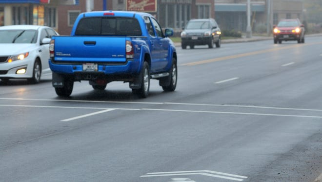 Traffic flows Monday  on the new pavement with a sharrow sign on Grand Avenue in Wausau.