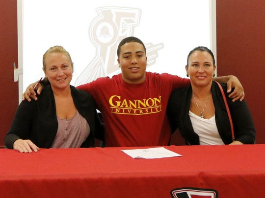 DaShaun Sutton is flanked by his mom, Katy Hyde, right, and his aunt, Rebecca Hyde, during Wednesday's signing ceremony at Elmira High School.