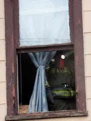 A firefighter opens second story windows to clear smoke
