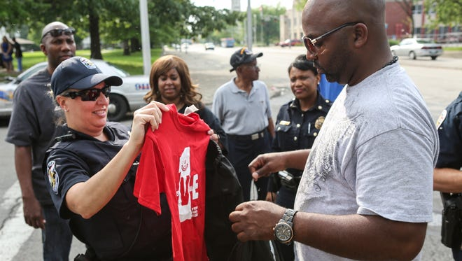 "Louisville Metro police officer Amanda Frederick, left, and Sgt. William LeFlore take OneLove Louisville T-shirts to hand out during a walk through the Beecher Terrace housing complex. ""The shirts are our motto,"" Safe and Healthy Neighborhoods staff member Rashaad Abdur-Rahman said. ""We really want each person to think and feel that they can be the one to reduce community violence."" May 11, 2016"