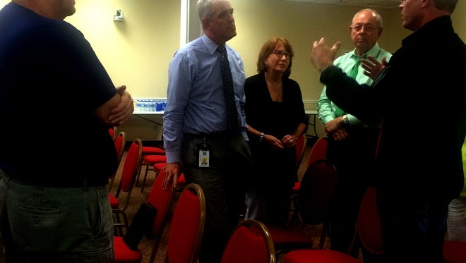 Mark Thessin, left, and Michael Phillips, right, discuss their problems with Eric Stuckey, Beverly Burger and Ken Moore.