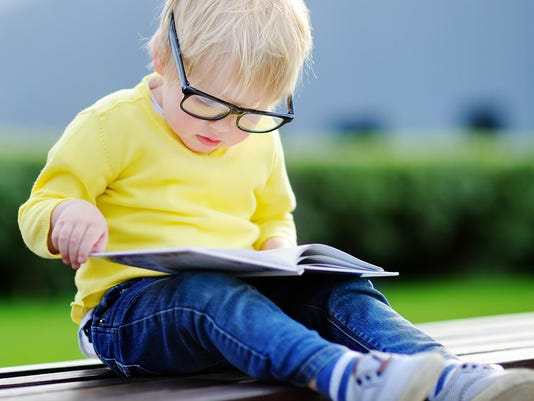 Toddler reading a book outdoors. Back to school concept