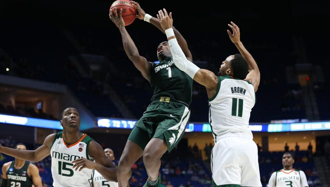 Mar 17, 2017; Tulsa, OK, USA; Michigan State Spartans guard Joshua Langford (1) goes up for a shot as Miami Hurricanes guard Bruce Brown (11) and center Ebuka Izundu (15) guard during the second half in the first round of the 2017 NCAA Tournament at BOK Center. Mandatory Credit: Kevin Jairaj-USA TODAY Sports