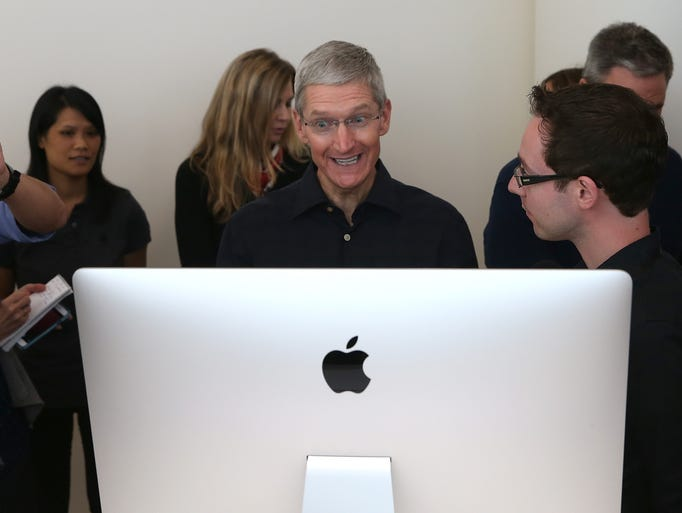 Apple CEO Tim Cook looks during a new 27 in. iMac with