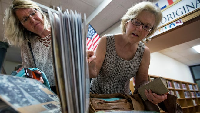 Deb Weis, left, who graduated from the school in 1973, and Donna Cook, who graduated in 1968, look through old photos during the End of East Community Open House at East Junior High School in Wisconsin Rapids, Wis., May 30, 2018.