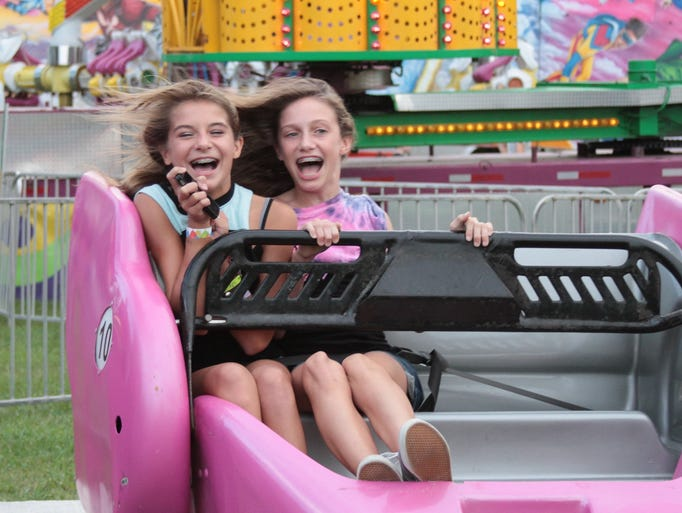 Lily Gordon, 12, Lakyn Paschall, 12, ride the Scrambler at the fair in Trenton on Tuesday night.