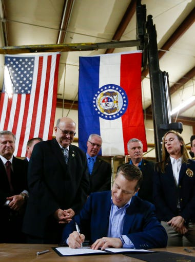"Flanked by fellow lawmakers, Missouri Gov. Eric Greitens signs legislation to make Missouri the 28th ""right-to-work"" state during a ceremonial signing at the abandoned Amelex warehouse in Springfield, Mo. on Monday, Feb. 6, 2017. The law, which goes into effect on Aug. 28, prohibits unions from charging membership dues as a condition of employment."