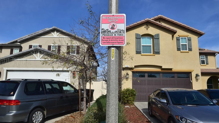 A Neighborhood Watch sign is attached to a pole in