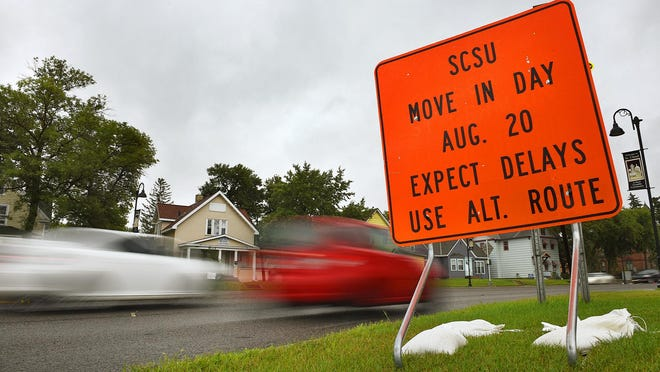 Motorists pass signs Tuesday along Ninth Avenue South warning about delays as students start moving in at St. Cloud State University later this week.