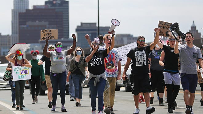 Protesters cross the All-America Bridge during a march Sunday in Akron against police brutality.