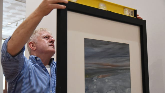 Rick Wilemon, graduate assistant for William Carey's Sarah Gillespie Museum of Art, hangs up watercolor pieces from artist Osmo Visuri's in the Oddfellows Gallery in downtown Hattiesburg.