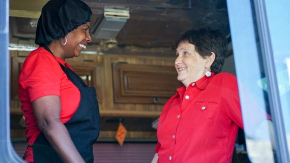 Sandra Matheson, left, learned to read with the help of volunteer Angela Fangue. Matheson recently passed her ServSafe test and opened her own food truck, Sandra's Creations.