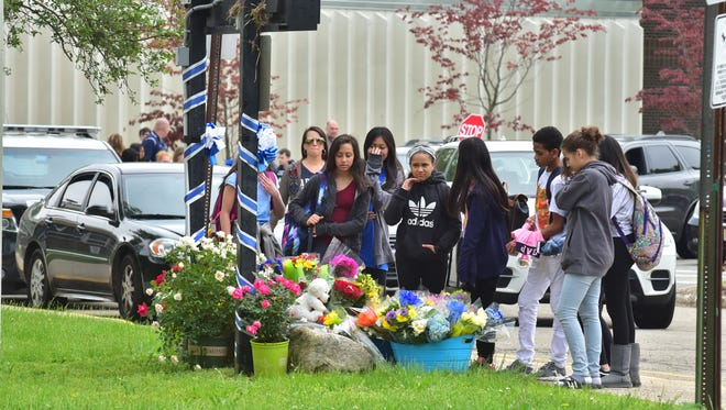 Students place flowers at a makeshift memorial at East Brook Middle School in Paramus, a day after a deadly school buss accident where 2 lives were lost.
