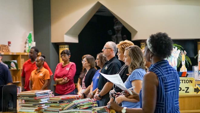 Employees from Home Furniture deliver school supplies to teachers Friday at Live Oak Elementary.