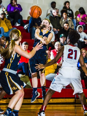 Makenzie Todd ,center, of Grand Ledge passes between Everett defenders to teammate Allyson Hunt ,left, in the paint during their game Friday January 29, 2016 in Lansing. KEVIN W. FOWLER PHOTO