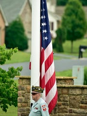 VFW 1599 Honor Guard member Mickey Finn stands beside a flagpole that was dedicated to Capt. Charles Bolan on Thursday, June 23, 2016 at Northfield at Menno Haven.