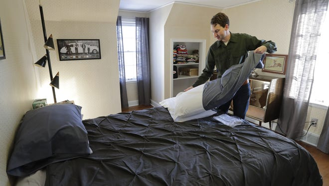 Airbnb host Joshua Skog changes linens in a room at his Neenah home in preparation for a guest.