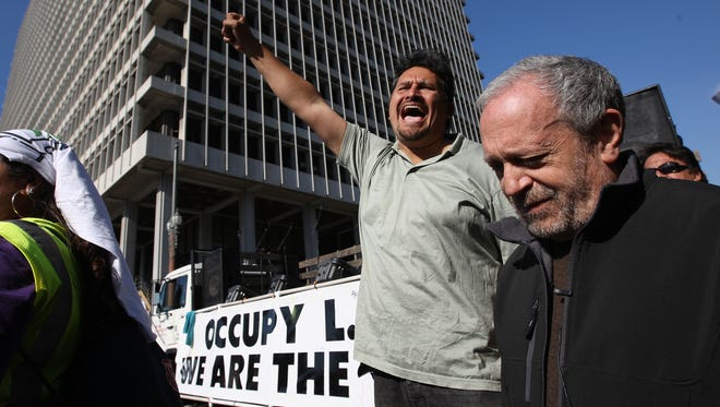 In 2011, former Labor Secretary Robert Reich, right, is cheered as he is introduced to speak to Occupy Los Angeles protesters.