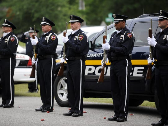 Lafayette police officers stand at attention while taps is played after the 21 gun salute Thursday at St. Barnabas Episcopal Church in Lafayette. Law enforcement officers from Lafayette and the surrounding area as well as family members of officers killed in the line of duty attended the service for Police Memorial Day.