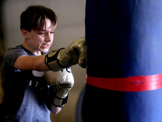 Caelan Berry, 13, works the heavy bag during his workout